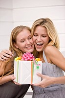 Woman giving a present to her friend (thumbnail)