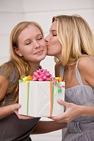 Woman giving a present to her friend and kissing