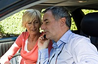 Man with his wife in a car and talking on a mobile phone