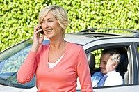 Woman talking on a mobile phone and her husband in a car in the background