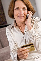 Portrait of a woman talking on a mobile phone and holding a credit card