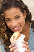 Portrait of a girl holding a sandwich and smiling (thumbnail)