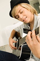 Teenage boy playing a guitar