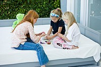 Three girls playing with toys on the bed
