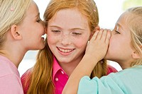 Two girls whispering to another girl