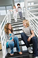 Boy and a teenage girl gossiping on a staircase