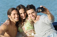 Three friends taking a picture of themselves with a digital camera