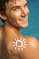 Man with sun shape on his shoulder at the poolside