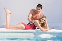 Man rubbing woman's back at the poolside