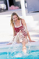 Woman sitting at the poolside and splashing water (thumbnail)