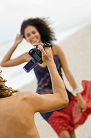 Man making a video of a woman on the beach