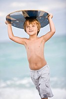 Boy holding a body board over his head