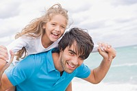 Man giving his daughter piggyback on the beach (thumbnail)