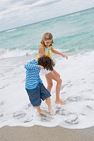 Boy playing with a girl on the beach