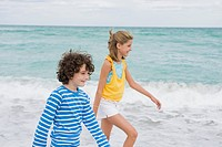 Boy walking with a girl on the beach