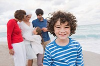 Boy smiling with his family standing behind him on the beach