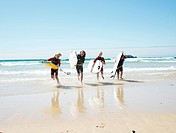 Three girls and a boy running across the beach, with surfboards, Bretagne, France, Europe