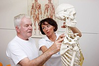 Therapist explaining to a patient the anatomical basis for physical therapy, based on a skeleton, physical therapy department in a hospital, inpatient...