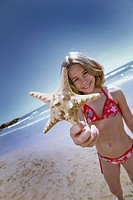 girl on the beach with starfish