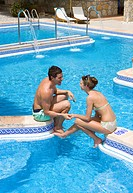 Couple holding hands and sitting at edge of swimming pool
