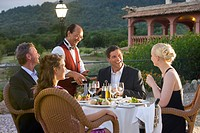 Waiter pouring wine for well_dressed couples at table on restaurant balcony