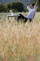 Happy businessman with arms raised looking at laptop on table in rural field