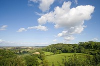 Clouds in blue sky over scenic view of countryside