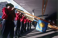 Photograph of a row of swiss men playing the Alpenhorn in Switzerland