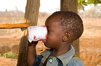 Boy drinking fresh milk from a cup, Magoye, Mazabuka, Zambia, Africa