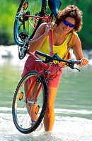 cyclist carrying bicyle through brook, wearing sunglasses