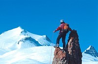 mountaineer standing on jagged rock tower, with snow_capped mountain in background, France, Vanoise NP