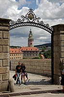 Young couple entering the castle complex through a gate, Ceský Krumlov, Czech Republic, Europe