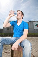 Young man drinking in front of an industrial site