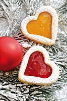 Heart-shaped short pastry jam biscuits and a red Christmas tree ball on a fir branch