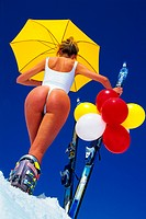female skier wearing white body, snow bunny holding ski and yellow sun shade, colourful balloons fixed at the ski