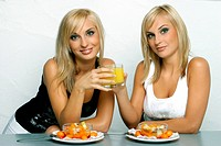 blond twins chinckling with glasses filled with orange juice.