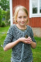 Young girl with baby duck on her hand