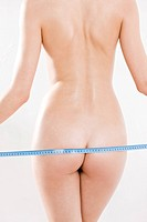 nude woman measuring hips