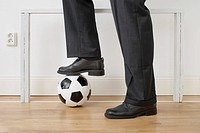 detail of businessman standing in front of goal at home