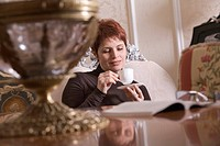 mature woman sitting in living room drinking coffee