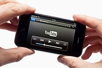 Male hands holding apple iPhone watching a video clip loading showing YouTube logo