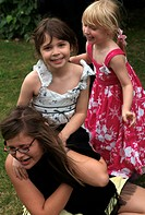 Family Aunt and two Nieces Playing at a Wedding reception in a Garden after Wedding in Peterborough England