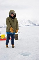 Moose, Wyoming - Jenny Gillette, 92 years old, fishes on the ice of Jackson Lake in Grand Teton National Park, with the temperature below zero degrees...