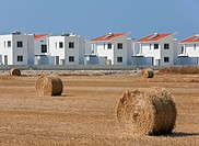 Straw bales in a field, in the back cottages, symbolic for agriculture and tourism, Pervolia, Southern Cyprus, Cyprus, Europe