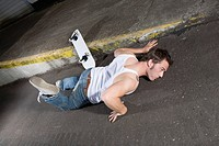 Skateboarder lying on asphalt in a weird position