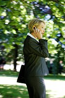 Woman wearing a ladies' suit, trouser suit, businesswoman, early 40s, on her mobile, outdoors, carrying a laptop