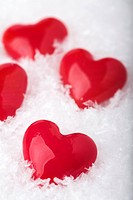 Red hearts made of glass in artificial snow