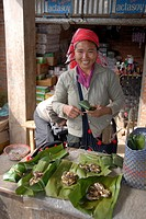 Market woman of the Phunoi ethnicity selling grilled fish in banana leaves, market in Phongsali, Laos, Southeast Asia