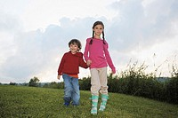 Young boy and girl walking towards camera holding hands.