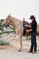 man saddling up horse